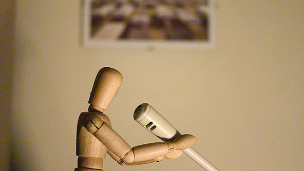 puppet holding desk microphone.